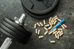 Doping in sport. Syringe and dumbbell Royalty Free Stock Photos