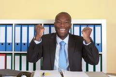 Dopingu afrykański businssman z błękitnym krawatem przy biurem obrazy royalty free