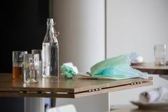Dopo il pranzo di compleanno - bottiglia di acqua e vetri che si siedono sulla tavola con la borsa abbandonata del regalo e della fotografia stock