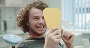 Dopo paziente sorridente di visita del dentista il giovane davanti allo specchio nella stanza dentaria della clinica dopo un'igie stock footage