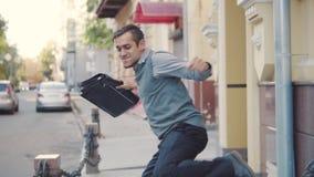 Dopo un riuscito affare, un giovane uomo d'affari con una cartella imbroglia intorno, getta sulla sua cartella e si diverte stock footage
