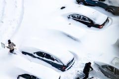 Dopo una bufera di neve, la gente scava fuori le automobili da sotto neve Immagini Stock Libere da Diritti