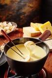 Doppa in i en smaklig ostfondue med bröd royaltyfri foto