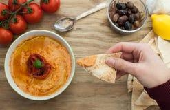 Doppa pitabröd i hummus arkivbilder
