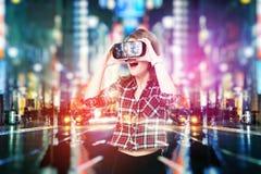 Doppelbelichtung, das junge Mädchen, das Kopfhörer der Erfahrung VR erhält, benutzt vergrößerte Wirklichkeitsgläser und ist in ei Lizenzfreies Stockfoto