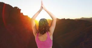 Doppelbelichtung der Frau mit den Händen umklammerte die Ausführung von Yoga auf Bergen stockfotos
