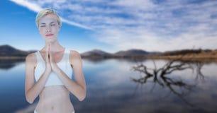 Doppelbelichtung der Frau mit den Händen umklammerte die Ausführung von Yoga gegen See lizenzfreies stockfoto