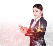Doppelbelichtung der Geschäftsfrau, die intelligentes Telefon mit Stadtba verwendet stockfotos