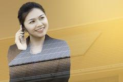 Doppelbelichtung der Geschäftsfrau, die Telefon mit Solardach verwendet Stockfotos