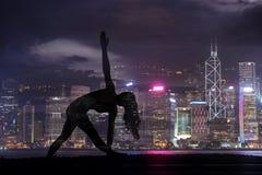 Doppelbelichtung der Schattenbildyogafrau gegen Hong Kong-Stadt stockfotos