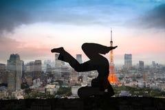 Doppelbelichtung der Schattenbildyogafrau gegen Tokyo-Stadt stockfotos