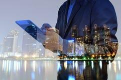 Doppelbelichtung der Stadt und des Geschäftsmannes, der digitale Tablette verwendet stockfotografie