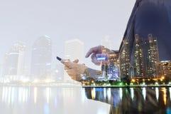 Doppelbelichtung der Stadt und des Geschäftsmannes, der digitales smartphon verwendet stockfotografie
