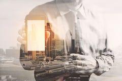 Doppelbelichtung des Erfolgsgeschäftsmannes unter Verwendung des intelligenten Telefons mit Lo lizenzfreie stockbilder