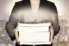 Doppelbelichtung des Geschäfts Bücher mit Nachtstadtbild halten Lizenzfreie Stockbilder