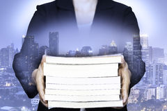 Doppelbelichtung des Geschäfts Bücher mit Nachtstadtbild halten Stockfotos