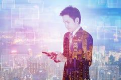 Doppelbelichtung des Geschäftsmannes, der intelligentes Telefon mit Stadtrückseite verwendet lizenzfreie stockfotos