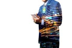 Doppelbelichtung des Geschäftsmanngriff Digital-intelligenten Tablets oder Smartphones mit moderner Stadt-Verkehrsszene stockfoto