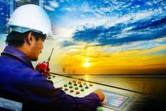 Doppelbelichtung des Ingenieurs arbeitend im Leitstelle- und Dämmerungshimmel lizenzfreies stockbild