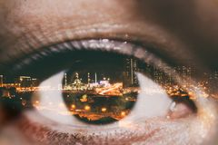 Doppelbelichtung des weiblichen Auges und der Nachtstadt von Dubai Lizenzfreie Stockfotografie