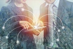 Doppelbelichtung von zwei Geschäftsleuten und von Stadt, Schauen auf tablep und Beratung über Projekt des Geschäfts, Konzept als  lizenzfreie stockfotos