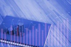 Doppelbelichtungs-Schritte des Münzenstapels und des Notizbuchpapiers auf Tabelle Lizenzfreies Stockfoto