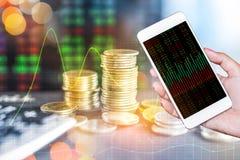 Doppelbelichtungshand, die intelligentes Telefon und Stapel Münzen über Börseschirm hält Stockfotos