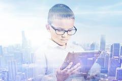 Doppelbelichtungsjungenstadt Student, der digitalen Tablettenskylinehintergrund verwendet Lizenzfreie Stockfotos