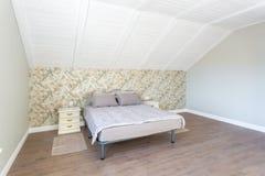 Doppelbett im Innenraum des modernen Schlafzimmers in der Dachbodenebene in der helle Farbart von teuren Wohnungen stockbild