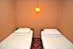 Doppelbetten im dunklen Hotelzimmer Stockfotografie