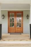 Doppelholztüren zu einem grünen Familienhaus Lizenzfreies Stockbild