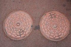 Doppelkanaldeckel auf dem Boden Stockbild