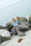 Doppelkinder, die auf Felsen am Strand spielen Stockfotos
