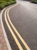 Doppelte gelbe Linien auf gebogener Straße lizenzfreies stockfoto