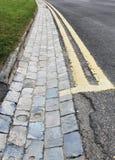 Doppelte gelbe Linien u. Ziegelstein-Straßenrinne Stockbilder