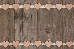 Doppelte Grenze von hölzernen Herzen und Band schnüren sich über Holz Lizenzfreies Stockfoto