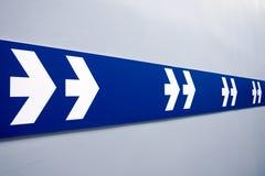 Doppelte weiße Pfeile unterzeichnen auf dem blauen Streifen, der zeigt, um herauszunehmen stockfoto