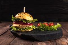Doppelter Burger auf dem Brett auf schönem schwarzem hölzernem rustikalem Hintergrund Lizenzfreies Stockbild