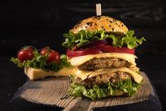 Doppelter Burger auf dem Brett auf schönem schwarzem hölzernem rustikalem Hintergrund Stockbilder