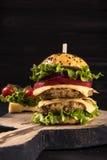Doppelter Burger auf dem Brett auf schönem schwarzem hölzernem rustikalem Hintergrund Lizenzfreie Stockfotografie