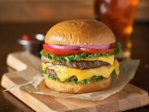 Doppelter Cheeseburger mit Kopfsalat, Tomate, Zwiebel stockbilder
