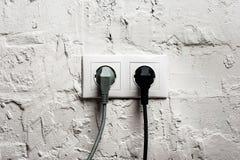 Doppelter elektrischer Sockel mit verstopften Kabeln Lizenzfreies Stockfoto