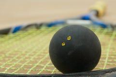 Doppelter gelber Punktsquashball auf einem Schläger Stockbilder