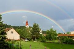 Doppelter Regenbogen über einer Kirche in einem Dorf Lizenzfreie Stockfotos