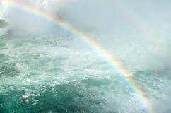 Doppelter Regenbogen über Fluss und Wasserfall Stockfotografie