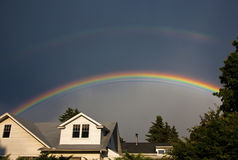 Doppelter Regenbogen über Häusern Stockbild