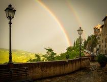Doppelter Regenbogen über Lampost in Umbrien, Italien Stockbilder