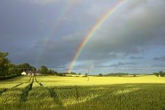 Doppelter Regenbogen über sonnenbeschienen Feldern, schottische Grenzen, Schottland Stockbild