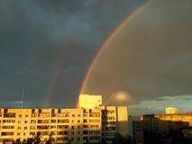 Doppelter Regenbogen und UFO über der Stadt lizenzfreie stockfotos