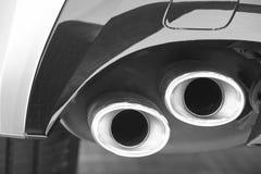 Doppeltes Autoauspuffrohrdetail in Schwarzweiss verunreinigung Stockfotografie